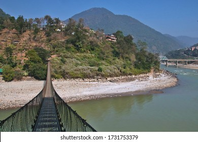 A suspension footbridge across the Trishuli river in Nepal at midday, with another bridge in the background
