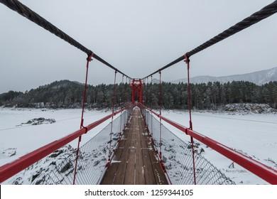 Suspension hanging bridge above winter frozen mountain Katun river, Altai mountains, Siberia, Russia