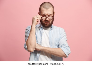 Suspicion. Doubt, mistrust, distrust concept. Doubtful man looking with disbelief expression . Young emotional man. Human emotions, facial expression concept. Studio. Isolated on trendy pink