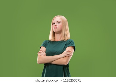 Suspicion. Doubt, mistrust, distrust concept. Doubtful woman looking with disbelief expression . Young emotional woman. Human emotions, facial expression concept. Studio. Isolated on trendy green