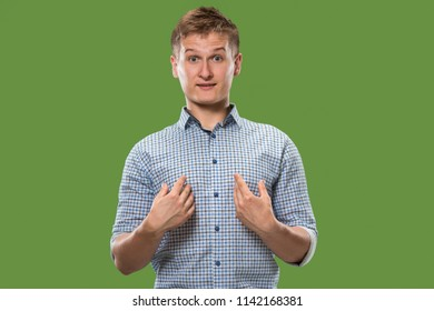 Suspicion. Doubt, mistrust, distrust concept. Doubtful man looking with disbelief expression . Young emotional man. Human emotions, facial expression concept. Studio. Isolated on trendy green
