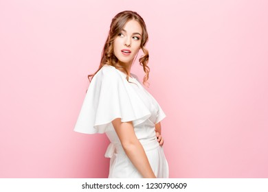 Suspicion. Doubt, mistrust, distrust concept. Doubtful woman looking with disbelief expression . Young emotional woman. Human emotions, facial expression concept. Studio. Isolated on trendy pink