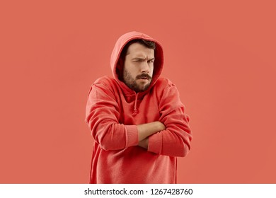 Suspicion. Doubt, mistrust, distrust concept. Doubtful man looking with disbelief expression . Young emotional man. Human emotions, facial expression concept. Studio. Isolated on trendy coral