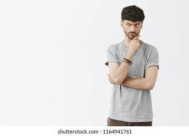 Suspicious adult man with beard frowning and staring with disbelief and doubt left, being unsure if he can trust seller, holding hand on chin, lifting eyebrow hesitation during making up decision