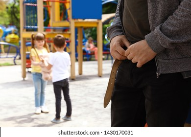 Suspicious adult man taking off his pants at playground with little kids, space for text. Child in danger