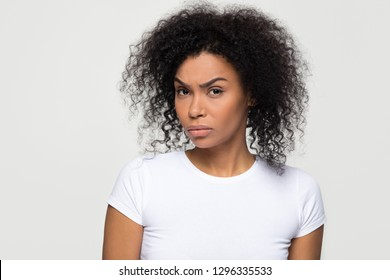 Suspicious annoyed young african american woman with distrustful face looking at camera, skeptical sarcastic black girl feeling cautious dubious distrusting isolated on grey white studio background