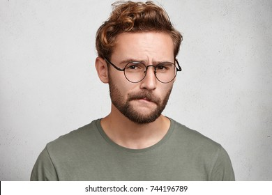 Suspicious bearded man looks doubtfully, curves lips, being indecisive, makes grimace, tries to find solution. Uncertain upset pensive male hesitates what to buy. Facial expressions concept.