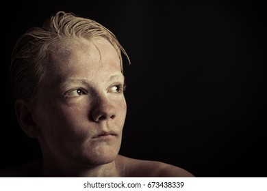 Suspicious blond boy stares into the light that strikes the left side of his face against a black background