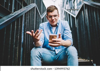 Suspicious caucasian young man in eyeglasses reading strange message on smartphone about notification with problem after payment offer online on website.Sceptical male blogger watching dislike video
