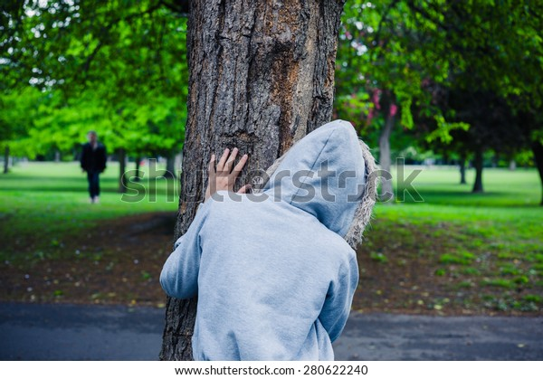 A suspicious character wearing a hoodie is hiding behind a tree in the park