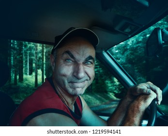 A suspicious driver behind the wheel invites the passenger to his car. The concept of danger of hitchhiking.