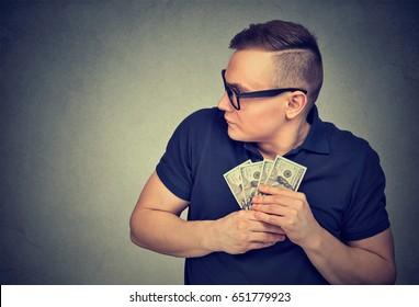 Suspicious greedy man grabbing money