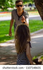 Suspicious Man enticing little child girl in the park playground.Danger of kidnapping kid.