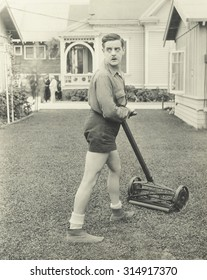 Suspicious man with a push reel lawn mower
