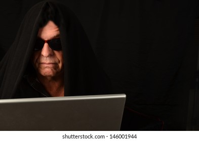 Suspicious man with sunglasses on computer/Identity Thief/Man with a black shroud on his computer
