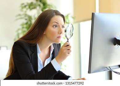 Suspicious office worker checking online content on computer using a magnifying glass