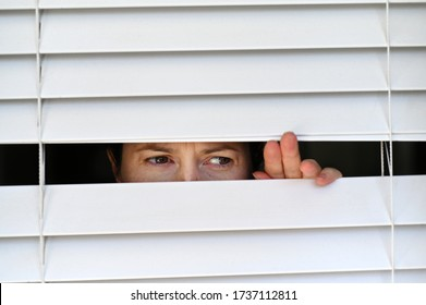 Suspicious person looking outside home window from behind Venetian curtains. Concept photo of person that have Pistanthrophobia and Agoraphobia, a person who don't trust fear of leaving the house.