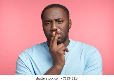 Suspicious serious Afro American male in casual t shirt, touches lips as thinks about something, tries to get brilliant idea. Young businessman deep in thoughts how to rise sales and profits