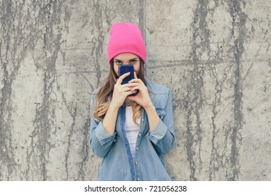 Suspicious or shy woman in casual clothes and pink hat hiding her face behind smartphone, she read secret information. The woman is standing on the street against grey background