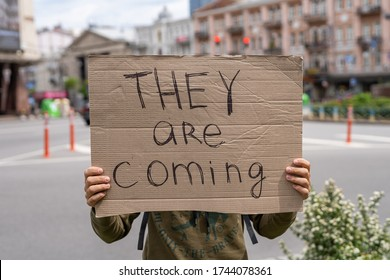 suspicious and warning inscription on sign. They are coming. Hands holding banner outside on city streets. social protest motivation concept. Guy with sign imitation. Aliens guests waiting invitation