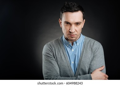 Suspicious young man looking angrily on camera