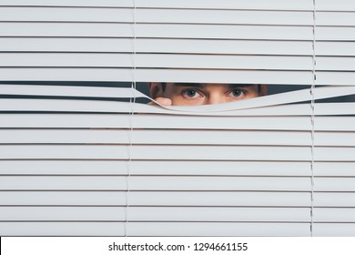 suspicious young man peeking and looking at camera through blinds, mistrust concept
