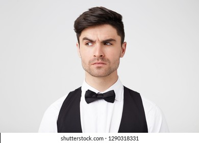Suspiciously looking attractive brunet with small stubble looks quizzically, incredulously aside, one eyebrow raised, smartly dressed, isolated over white background