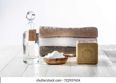 Sustainable cleaning laundry with chic homemade detergents and softener with traditional Marseille soap, vinegar and baking soda for fluffy folded towels on wooden background