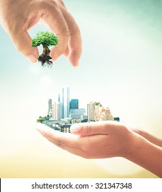 Sustainable development goals concept: Two human hand holding big tree and city on blurred nature background