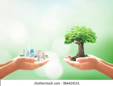 Sustainable development goals concept: Two human hand holding big city and tree over blurred green nature background