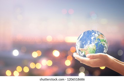 Sustainable Development Goals (SDGs) concept: Human hands holding earth globe over blur city background. Elements of this image furnished by NASA