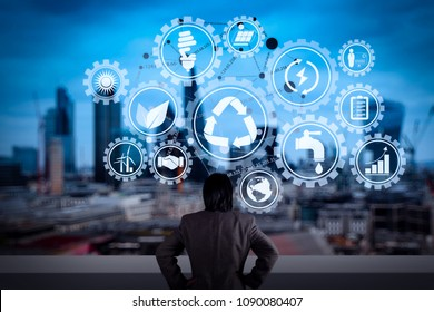 Sustainable development with icons of renewable energy and natural resources preservation with environment protection inside connected gears.businessman stands successfully on building.