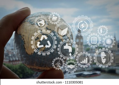Sustainable development with icons of renewable energy and natural resources preservation with environment protection inside connected gears.businessman hand showing texture the world.