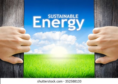 """Sustainable energy. Hand opening an old wooden door and found wording """"Sustainable energy"""" over green field and bright blue Sky Sunrise."""