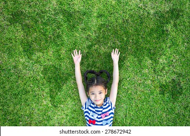Sustainable environment concept with healthy girl child having fun raising hands on eco friendly green grass lawn with world map