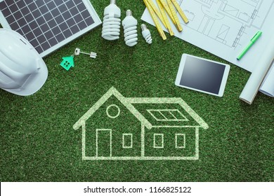 Sustainable house projects and green building concept: blueprint, solar panel and tools on lush grass