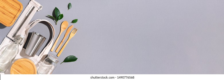 Sustainable lifestyle. Zero waste, plastic free shopping concept. Cotton bags, glass jar, bottle, metal cup, straws for drinking, bamboo cutlery and boxes on gray background. Banner.