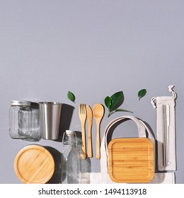 Sustainable lifestyle. Zero waste, plastic free shopping concept. Cotton bags, glass jar, bottle, metal cup, straws for drinking, bamboo cutlery and boxes on gray background
