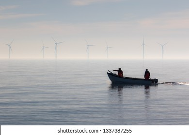 Sustainable resources alternative lifestyle. Small fishing boat with offshore wind turbines. Calm misty morning. Two fishermen heading out to sea. Tranquil landscape scene with beautiful background.