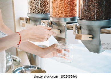 Sustainable shopping at small local businesses. Close-up image of woman pours red lentils in glass jar from dispensers in plastic free grocery store. Girl with cotton bag buying in zero waste shop.