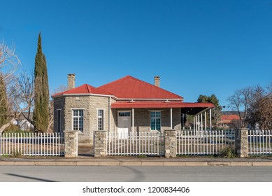 SUTHERLAND, SOUTH AFRICA, AUGUST 8, 2018: A street scene, with an old house with two chimneys, in Sutherland in the Northern Cape Province