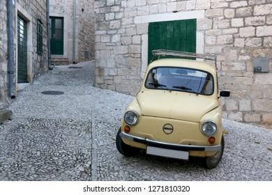 Sutivan, Croatia - December 31, 2018: Yellow vintage Zastava car, manufactured in the former Yugoslavia,  parked in a steep narrow cobblestone street in small town Sutivan, on island Brac, Croatia.