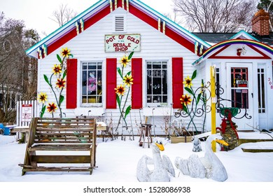 Sutton's Bay, Michigan / USA - February 10 2017: Bright red window shutters and house trim on a winter closed resale shop.