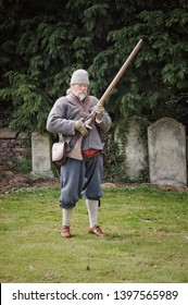 Sutton-St-James, England - May 06, 2019: A historical reenactor dressed as an English civil war musketeer raises his musket to fire
