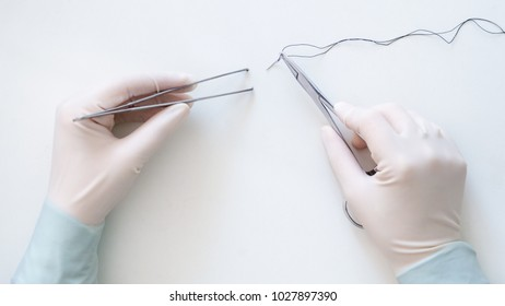 Suture using forceps and needle holder under the white background