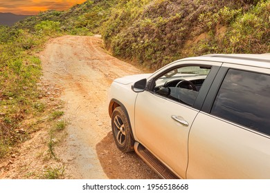 SUV car going up the sierra on a rocky road, white car on sloping ground during sunset.  Concept of eco tourism 4x4 adventure. Brazilian sierra of the Minas Gerais state.