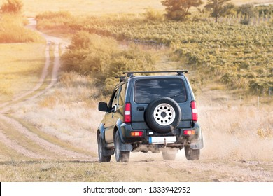 suv car offroad on dirt road in sunset