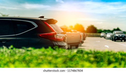 SUV Car parked on concrete parking area at factory near the sea with blue sky and clouds. Car dealership. Car stock for sale. Car factory parking lot. Automotive Industry. Used automobile business.