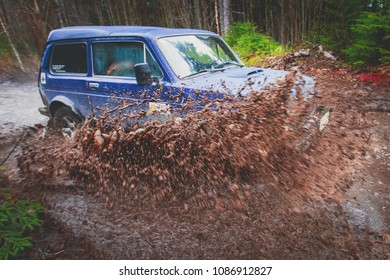 Suv offroad 4wd car rides through muddy puddle, off-road track road, with a big splash, during a jeeping competition