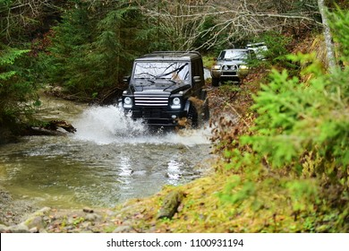 SUV or offroad cars crossing water stream. Car racing with creek on way. Extreme driving, competition and 4x4 vehicles concept. Offroad race in forest